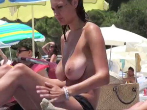 Sexy brunette with big natural tits at the beach