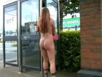 Busty blonde with pierced nipples and tattoos naked in a phone booth